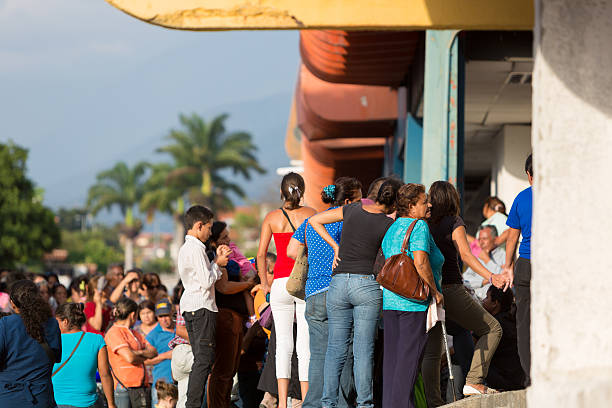 group of people waiting in line at public supermarket, venezuela - venezuela stock photos and pictures