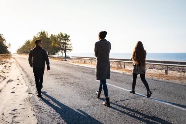 Groupe de personnes à pied le long de la route en bord de mer - Photo