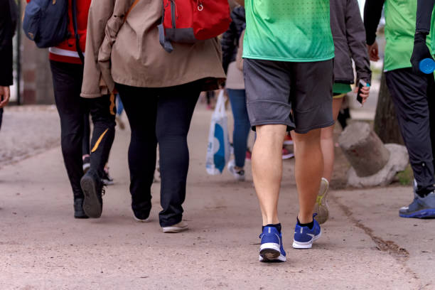 Group of people walk on the sidewalk, some with sports clothes stock photo