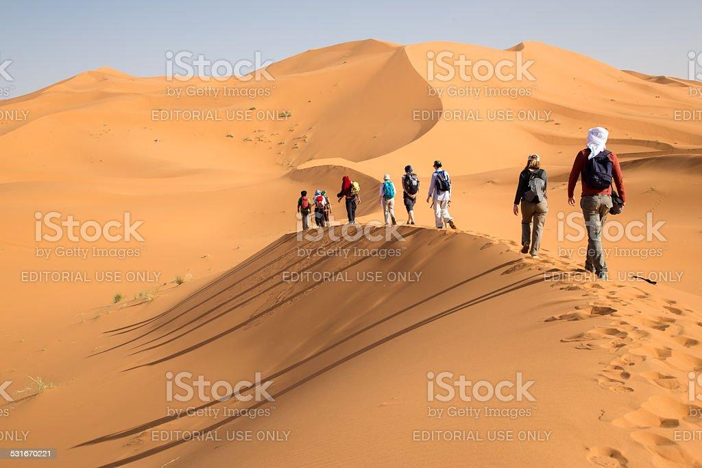 Group of people walking on sand dunes stock photo