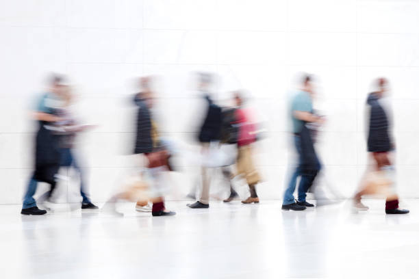 Group of People Walking on White Hallway, Motion Blur Effect stock photo