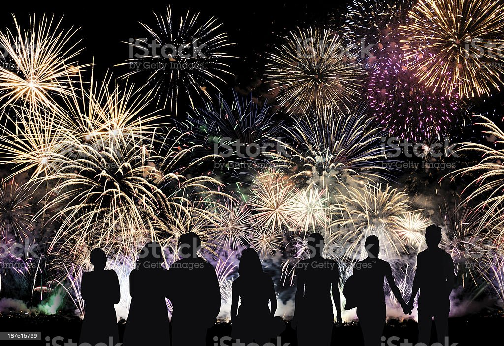 Group of people watch colorful holiday fireworks stock photo