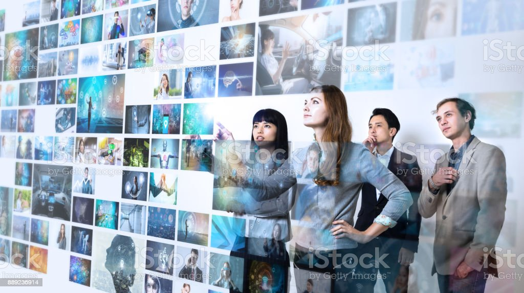 Group of people watching at a lot of pictures. Internet of Things. Information communication technology. stock photo