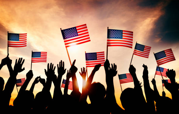 group of people waving american flags in back lit - happy 4th of july stock pictures, royalty-free photos & images