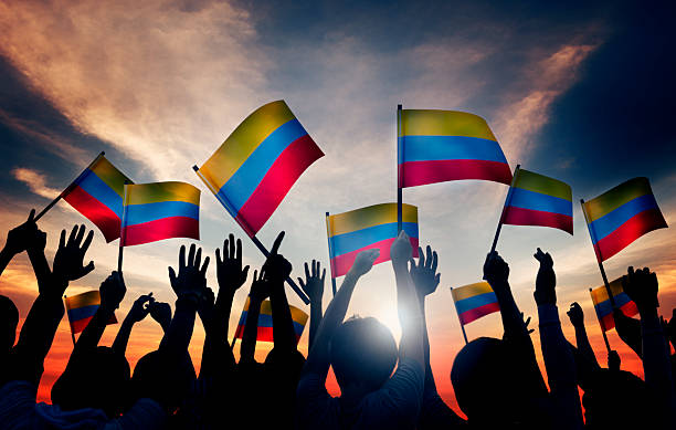 group of people waving columbian flags in back lit - colombia stock photos and pictures