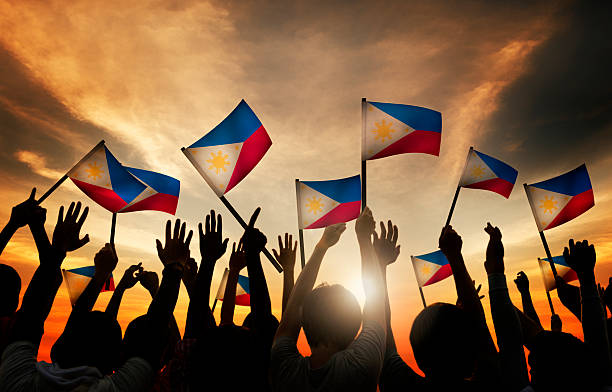 group of people waving filipino flags in back lit - philippines stock photos and pictures