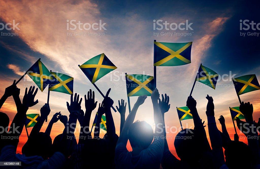 Grupo de pessoas agitando bandeiras da Jamaica em iluminação de fundo - foto de acervo