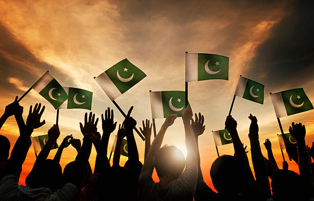 group of people waving flag of pakistan in back lit - pakistani flag stock photos and pictures