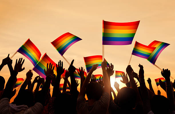 Group of People Waving Gay Pride Symbol Flags Group of People Waving Gay Pride Symbol Flags gay pride parade stock pictures, royalty-free photos & images