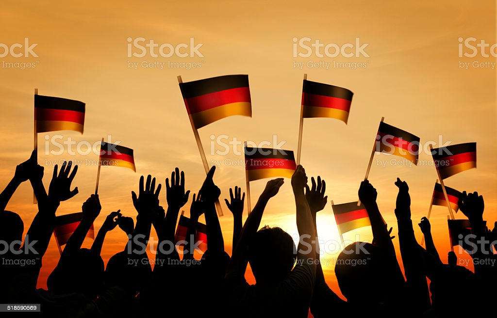 Group of People Waving German Flags in Back Lit stock photo