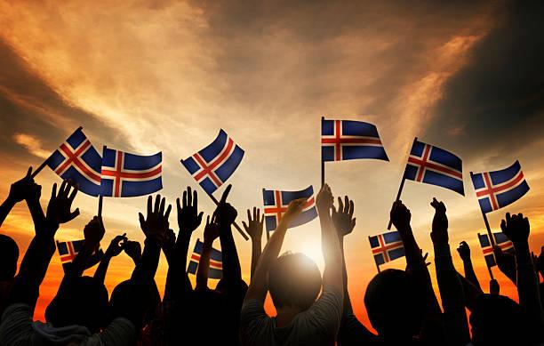 Grupo de pessoas agitando bandeiras na Islândia iluminação de fundo - foto de acervo