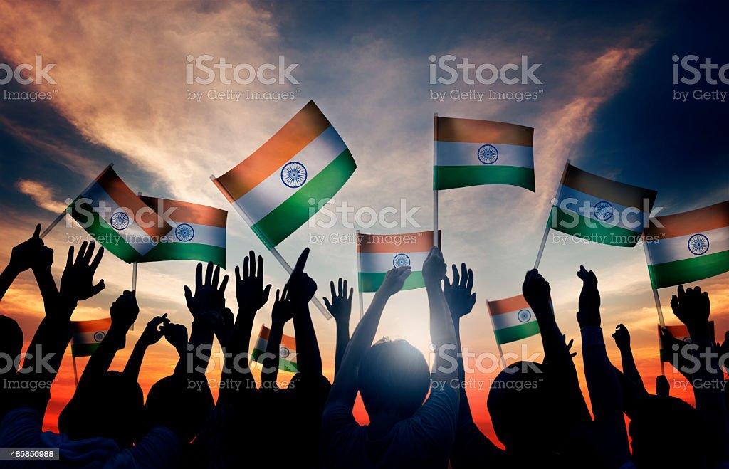 Grupo de pessoas agitando bandeiras Índico em iluminação de fundo - foto de acervo