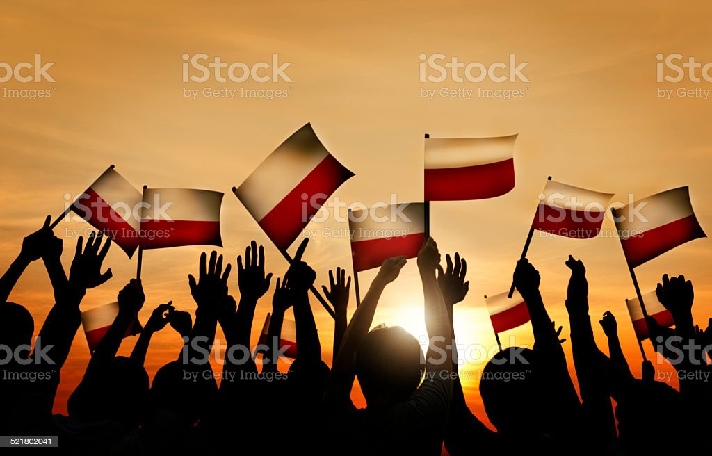 Group of People Waving Polish Flags in Back Lit stock photo