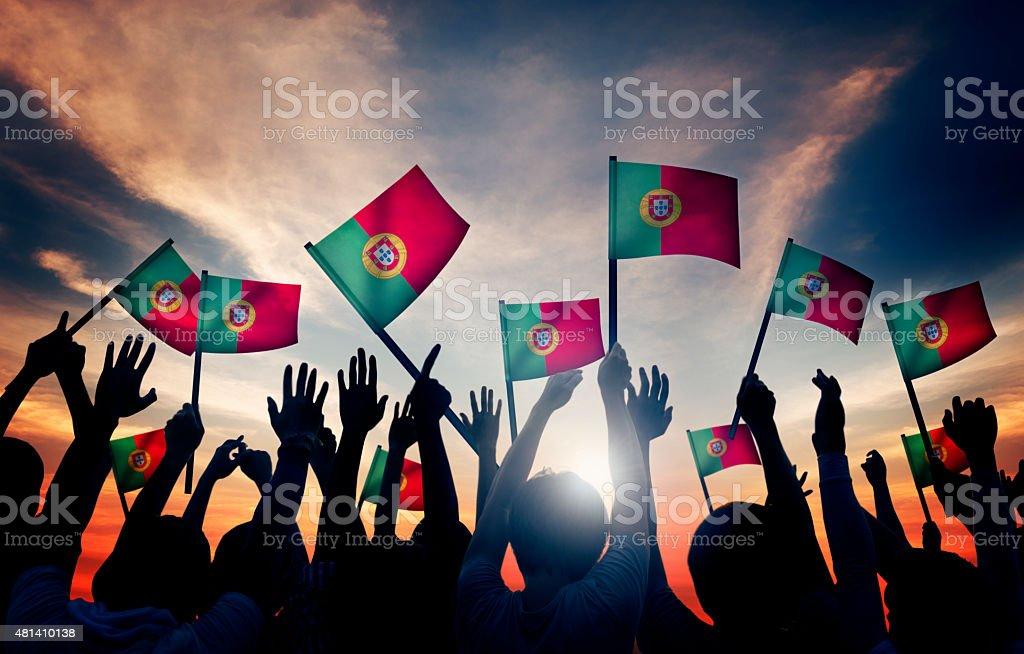 Grupo de pessoas a acenar bandeiras portuguesa em retroiluminado - fotografia de stock