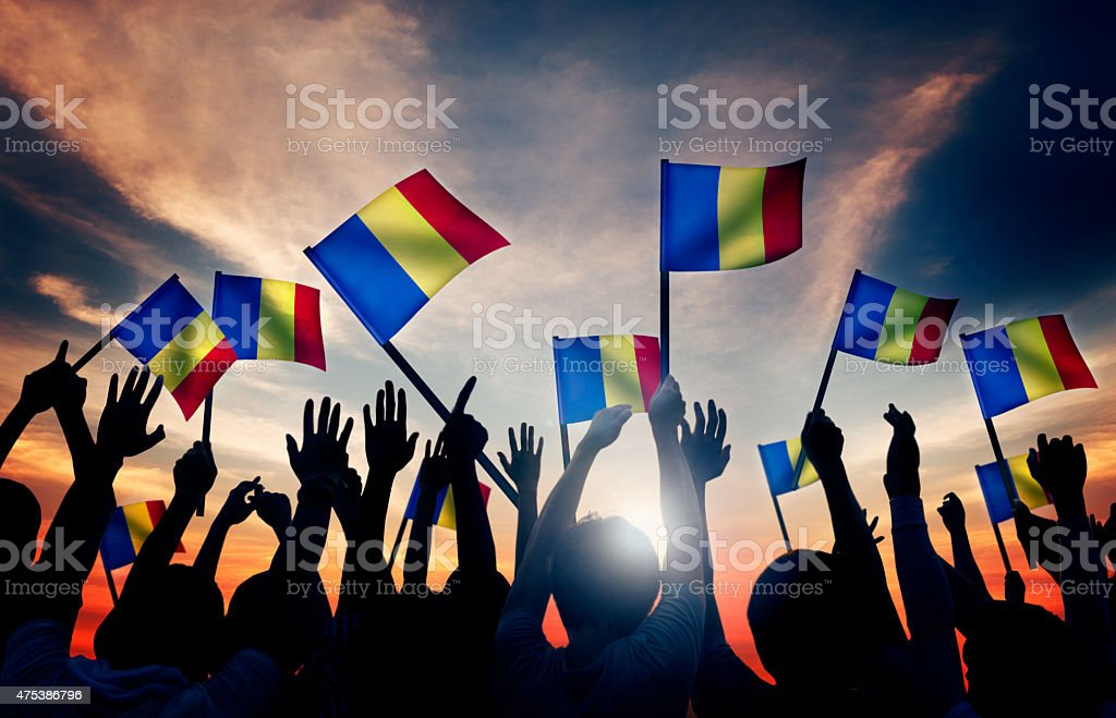 Group of People Waving Romanian Flags in Back Lit stock photo