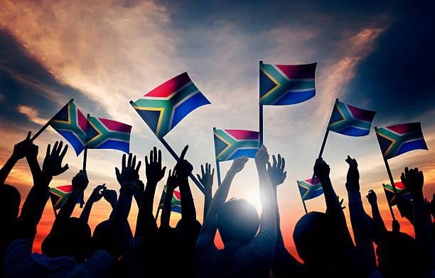 Gruppe von Menschen winken South African Flags im Gegenlicht – Foto