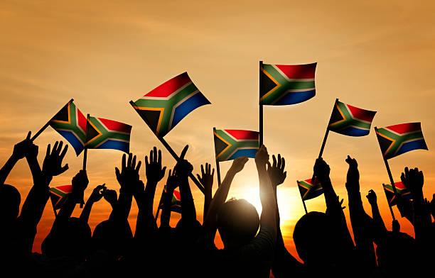 Grupo de personas, agitando South banderas africanas en Contraluz - foto de stock