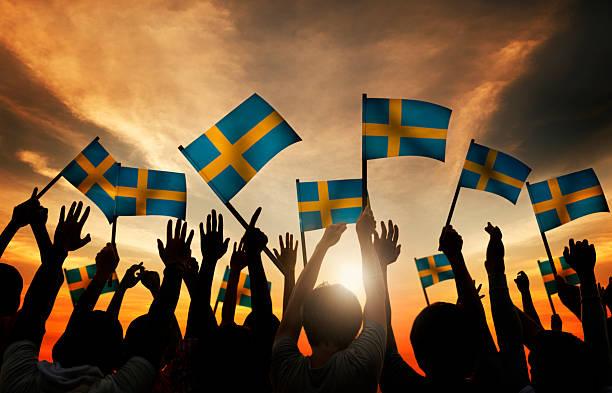 Grupo de pessoas agitando bandeiras sueca em iluminação de fundo - foto de acervo