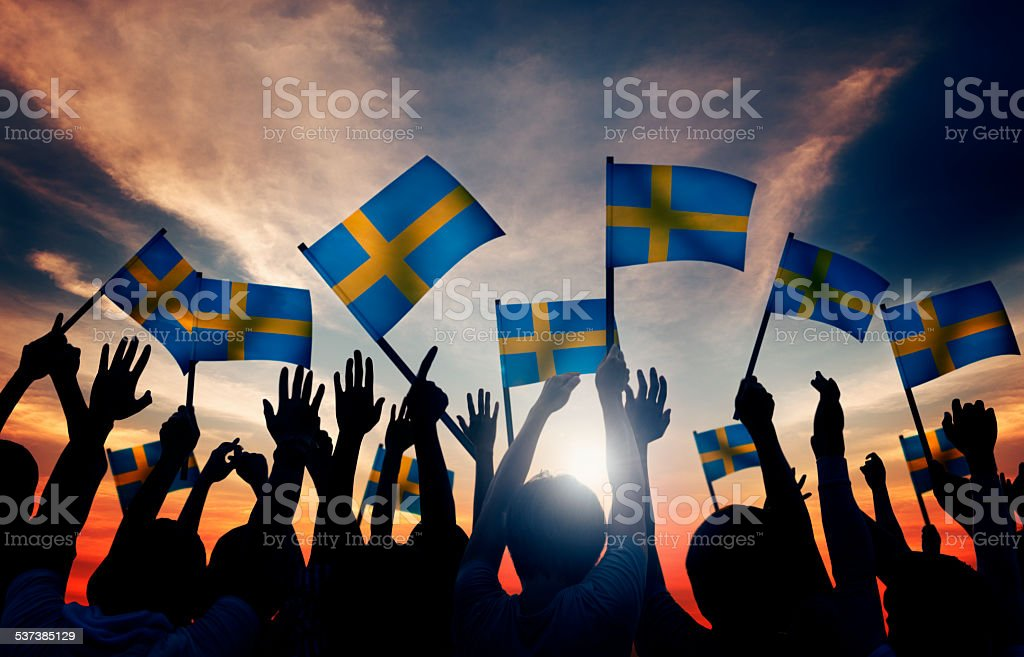 Group of People Waving Swedish Flags in Back Lit stock photo