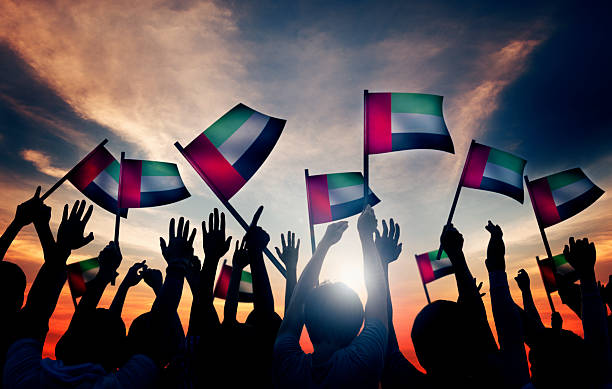 group of people waving the flag of uae - uae flag stok fotoğraflar ve resimler