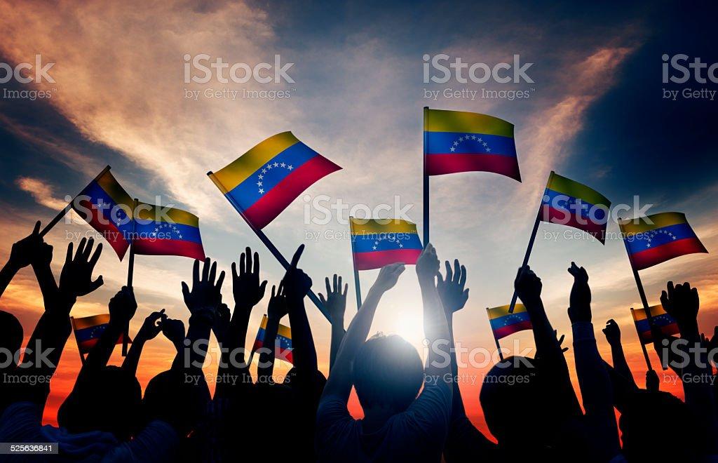 Group of People Waving Venezuelan Flags in Back Lit stock photo