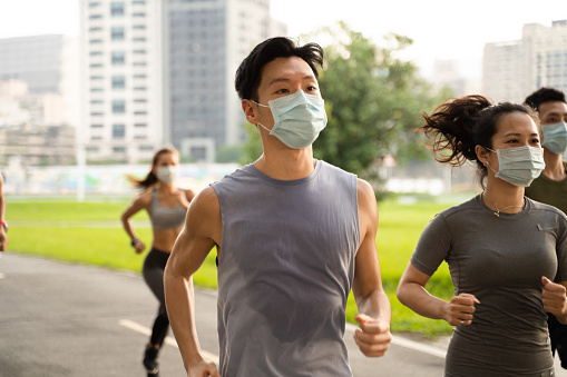 A group of people wear the masks running in the city.Health and fitness concept. covid19.