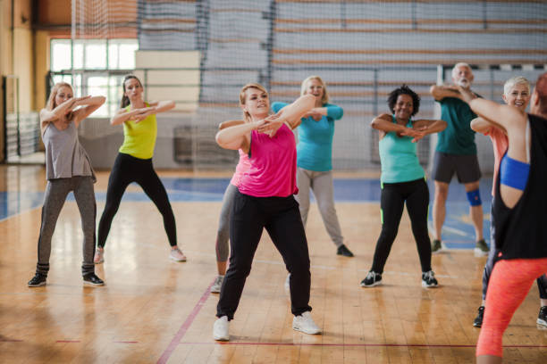 Group of people wearing colorful sports clothing dancing in gym stock photo