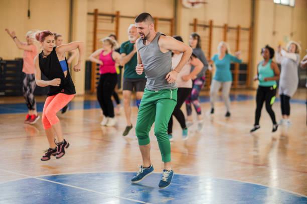 Gruppe von Menschen, die bunte Sportbekleidung tanzen im Fitnessstudio – Foto