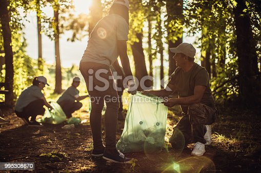 istock Group of people with garbage bags cleaning public park 995308670