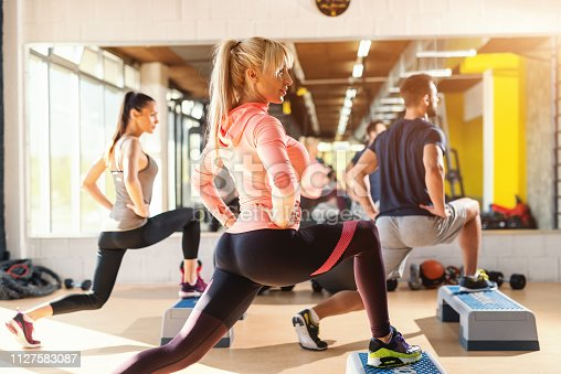 Group of people with healthy habits doing exercises for legs on steppers. Gym interior.