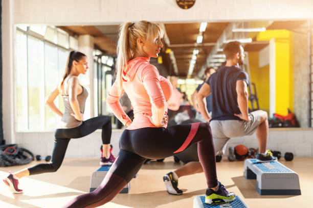 grupo de personas con hábitos saludables, hacer ejercicios para las piernas en steppers. interior del gimnasio. - aeróbic fotografías e imágenes de stock