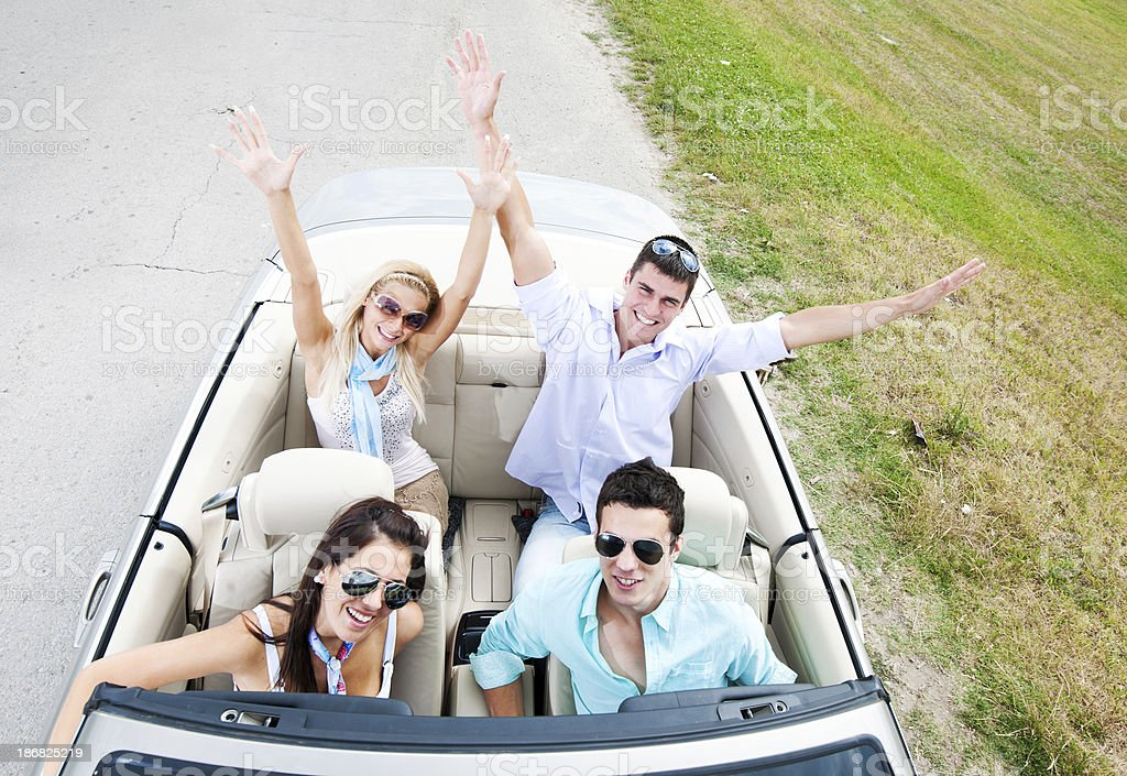 Group of people with raised hands driving in a cabriolet. royalty-free stock photo
