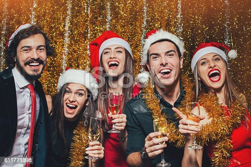 Group of cheerful people with champagne glasses wearing Santa hats on New Year party.