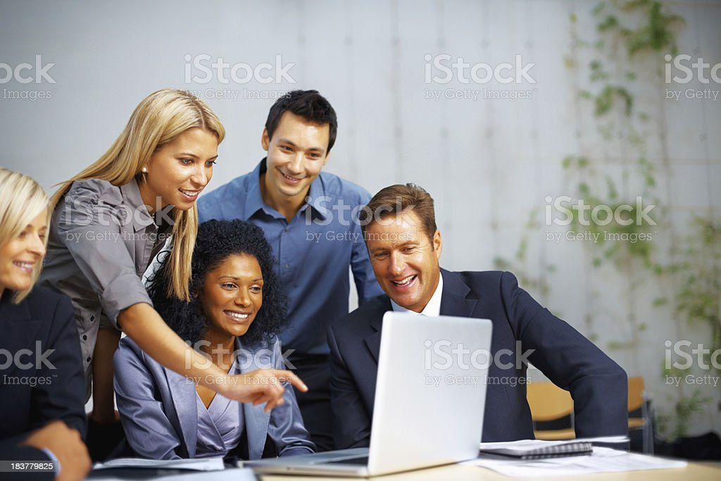 Group of people with woman pointing at laptop royalty-free stock photo