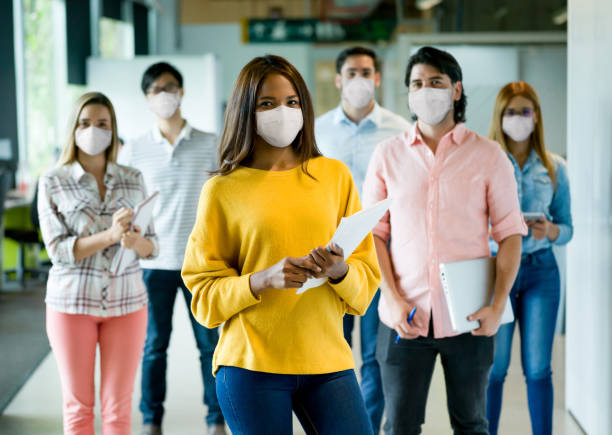 Group of people working at a creative office wearing facemasks stock photo