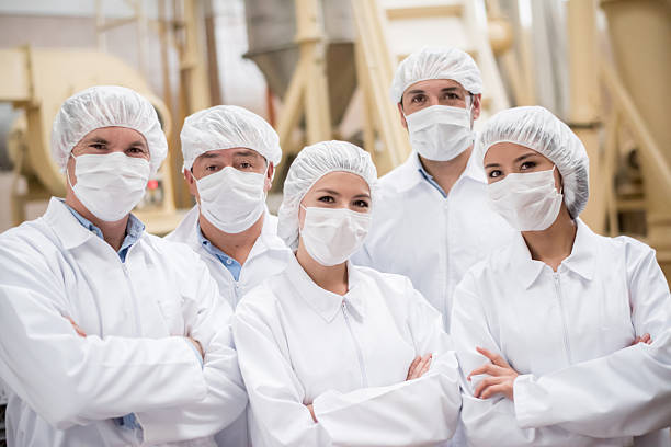 Group of people working at a food factory Group of Latin American people working at a food factory and wearing uniform hair net stock pictures, royalty-free photos & images