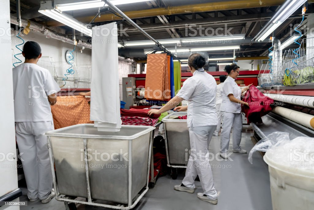 Group Of People Working At An Industrial Dry Cleaning