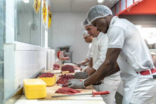 group of people working at the butchery - prodotti supermercato foto e immagini stock
