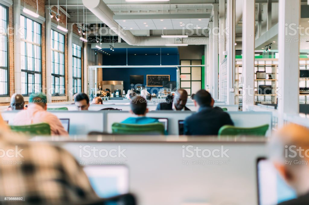 Group of people working in an open plan business. Startup. Bring your own device area. stock photo