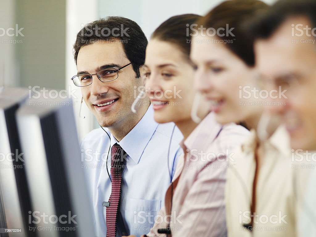 Group of people working on computers and talking on telephone headsets royalty-free stock photo