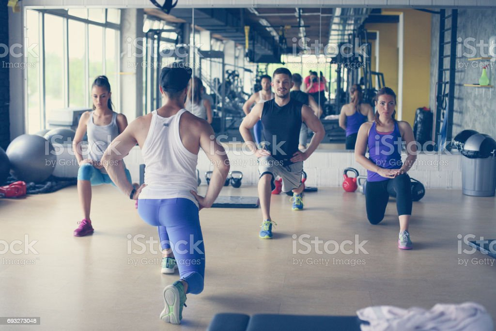 Group of people workout in healthy club. Young people stretching for legs. royalty-free stock photo