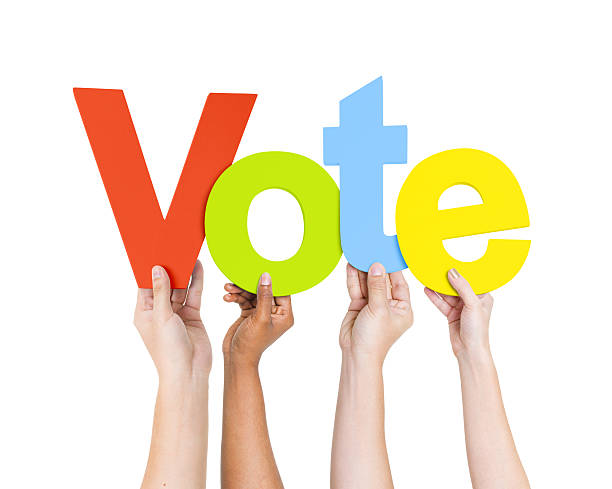 group of people's hands holding word vote - vote sign stock photos and pictures