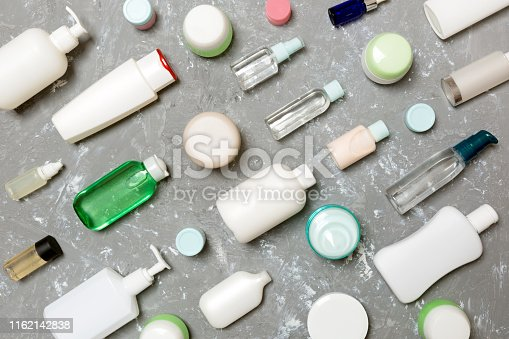 istock Group of plastic bodycare bottle Flat lay composition with cosmetic products on green background empty space for you design. Set of White Cosmetic containers, top view with copy space 1162142838