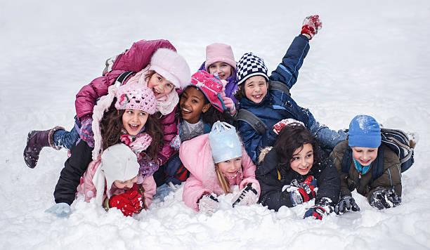 gruppe von fröhlichen kinder haben spaß im schnee. - schneespiele stock-fotos und bilder