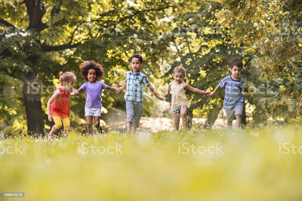 Group of playful children running together in the park. stock photo