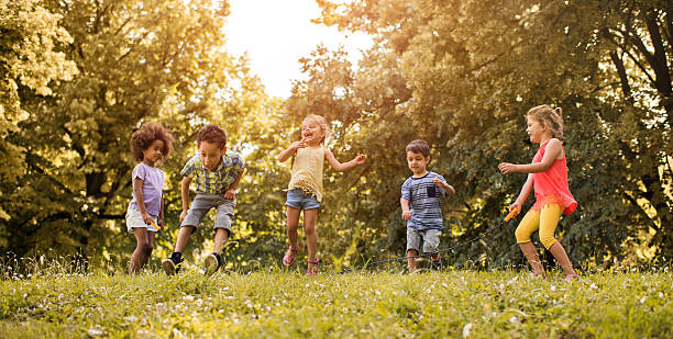 group of playful kids having fun while skipping jump rope. - african youth jumping for joy stock photos and pictures