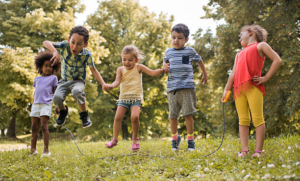 Group of playful kids having fun while skipping jump rope. stock photo
