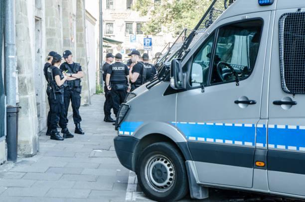 Gruppe von Polizisten stehen außerhalb der Station und diskutieren gemeinsam in Krakau während Sommertag – Foto