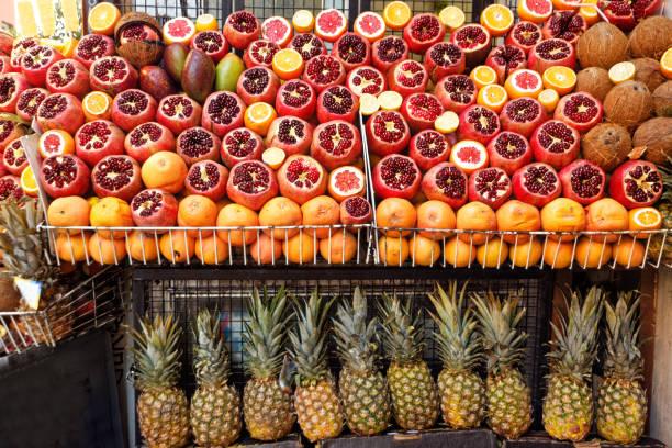 gruppe von granatäpfeln und grapefruits auf lebensmitteltheke - orangenscheiben trocknen stock-fotos und bilder