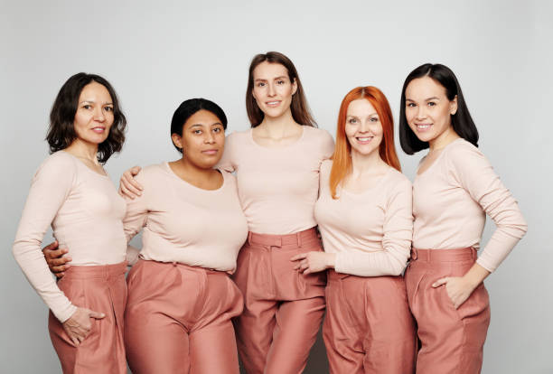 Group of positive natural multi-ethnic girls in beige sweaters and pink trousers cuddling together, womens society concept stock photo
